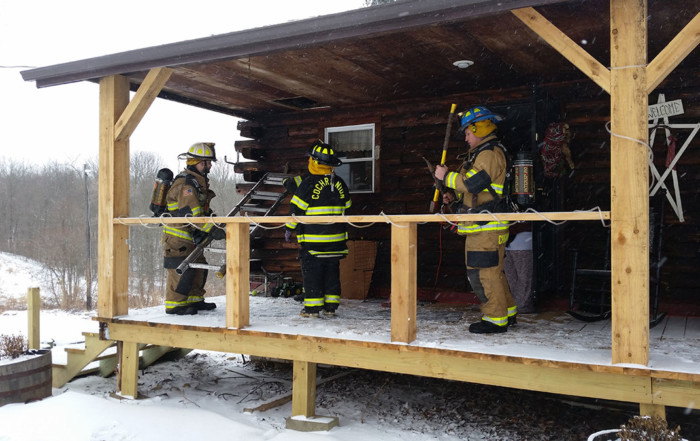 Firefighters gather equipment after a chimney fire on Lower Road in Mercer County