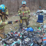 Firefighters Mike Rayburn and Kyle Corey use a portable tank and hand tools to extinguish a trash fire