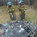 Firefighters Mike Rayburn and Kyle Corey use a water can to extinguish a backyard trash fire