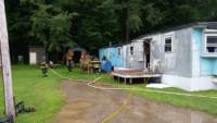 firefighters overhaul under trailer - Trailer Fire on Sugar Creek Lane