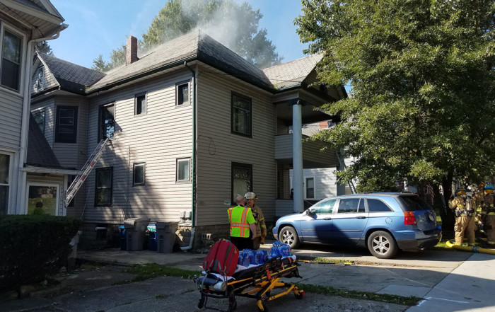 Smoke rises from the roof of a residential duplex on Baldwin St