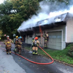 Burning embers shower down from a garage on fire during overhaul operations