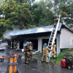 Firefighters overhaul a garage on fire on South St