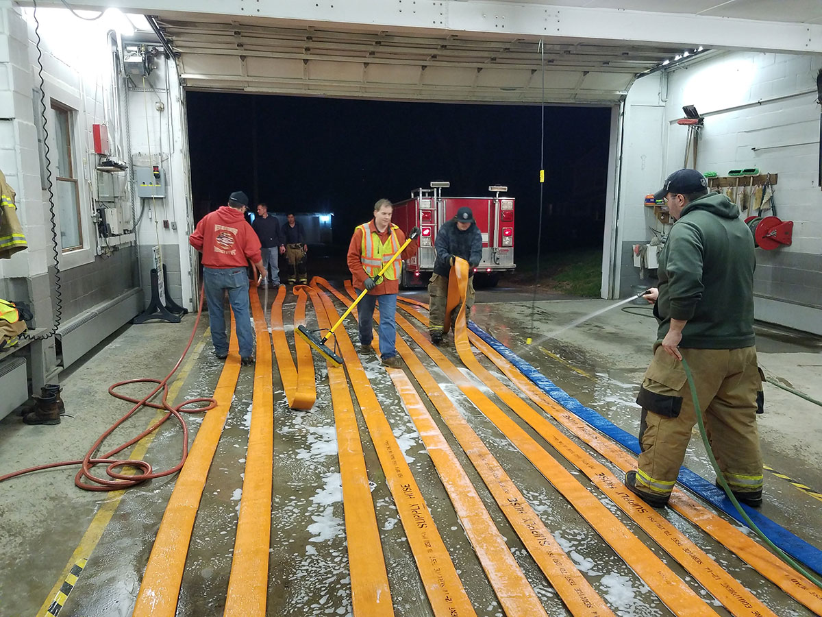 Firefighters wash supply hose from the pumping relay drill